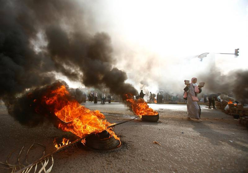 A Sudanese protester walks past burning tyres as military forces tried to disperse a sit-in outside Khartoum's army headquarters on June 3, 2019. - At least two people were killed Monday as Sudan's military council tried to break up a sit-in outside Khartoum's army headquarters, a doctors' committee said as gunfire was heard from the protest site. (Photo by Ashraf SHAZLY / AFP)