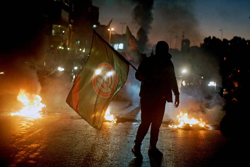 epaselect epa06484383 A supporter of Lebanese Parliament Speaker Nabih Berri and Amal movement carries the party's flag near burning tires during a protest in Beirut, Lebanon, 29 January 2018. Protests erupted following a row over a leaked video in which Foreign Minister Gebran Bassil allegedly calls Parliament Speaker Nabih Berri a 'thug' in a closed meeting at the southern suburb.  EPA/WAEL HAMZEH