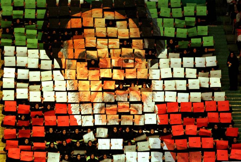 Girls in black uniforms hold up an image mosaic of Ayatollah Khomeini made up of individual boards, each in one of the three colors of the Iranian flag, 8th February 1999. They are in Azadi Stadium, west Tehran, during the celebrations on the 20th anniversary of the Islamic Revolution. (Photo by Kaveh Kazemi/Getty Images)