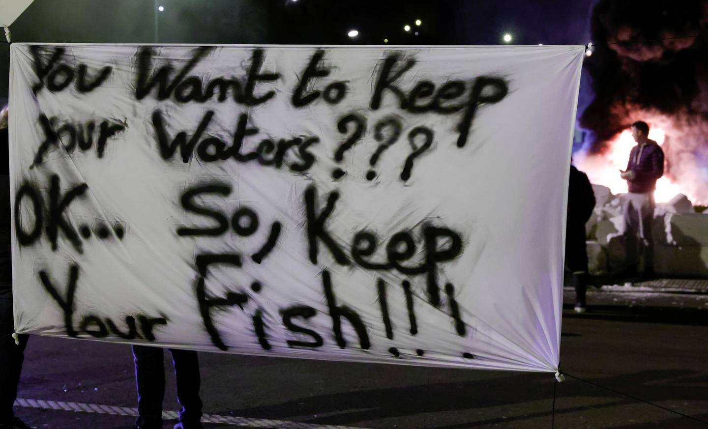 French fishermen hold a banner as they block lorries carrying UK-landed fish to protest for the slow issuance of licenses to fish inside British waters, at the fishing port in Boulogne-sur-Mer, France, April 23, 2021. REUTERS/Pascal Rossignol