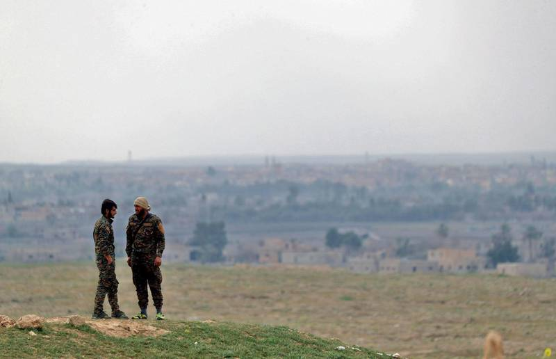 """Fighters with the US-backed Syrian Democratic Forces (SDF) stand at a position in the Baghouz area in the eastern Syrian province of Deir Ezzor on February 14, 2019 during an operation to expel hundreds of Islamic State group (IS) jihadists from the region.  Syrian fighters backed by artillery fire from a US-led coalition battled a fierce jihadist counteroffensive as they pushed to retake a last morsel of territory from the Islamic State group in an assault lasting days. More than four years after the extremists declared a """"caliphate"""" across large parts of Syria and neighbouring Iraq, several offensives have whittled that down to a tiny scrap of land in eastern Syria. / AFP / Delil souleiman"""