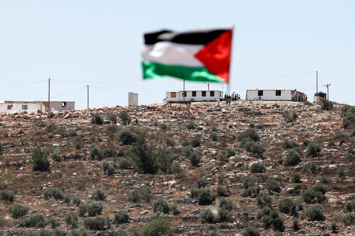 The flag of Palestine flutters on a rooftop across from the newly-built Israeli settler outpost in the village of Beita, south of Nablus in the occupied West Bank on June 18, 2021, following a protest against Israeli settlements. / AFP / ABBAS MOMANI
