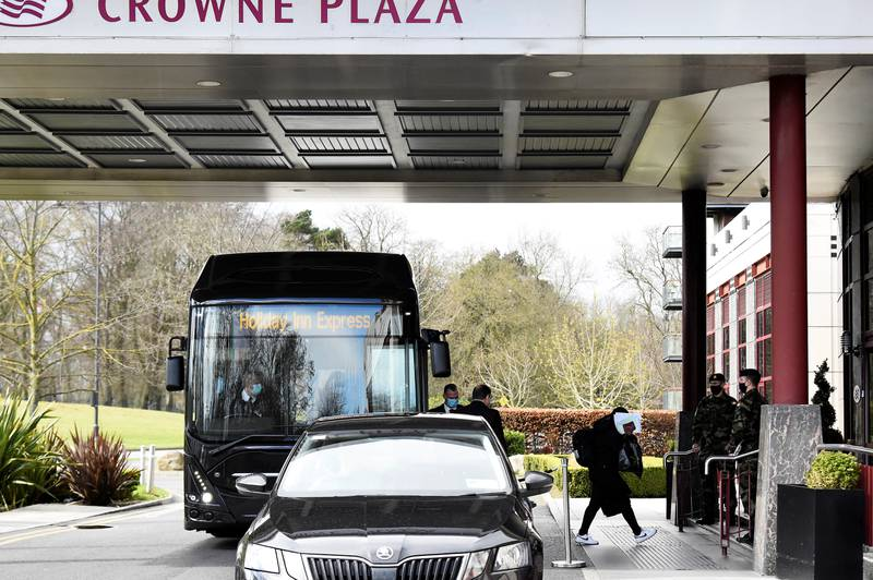 A passenger covers her face after getting off a designated quarantine bus at Crowne Plaza Dublin Airport Hotel, as Ireland introduces hotel quarantine programme for 'high-risk' countries' travellers, in Dublin, Ireland March 26, 2021. REUTERS/Clodagh Kilcoyne