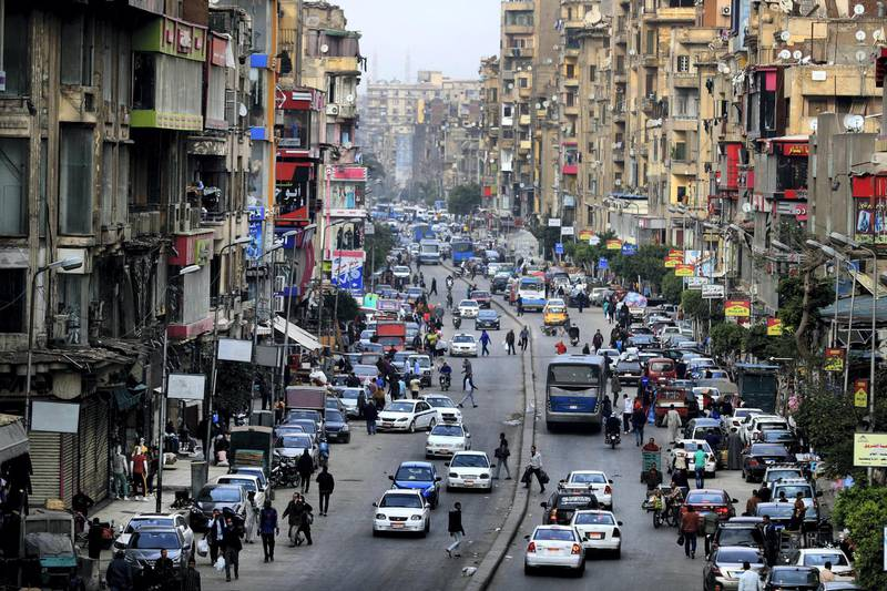 Cars pedestrians are pictured in one of the Egyptian capital Cairo's popular streets, shortly before the first day of a two-weeks night-time curfew imposed by the authorities to contain the spread of the novel coronavirus on March 25, 2020. (Photo by Khaled DESOUKI / AFP)