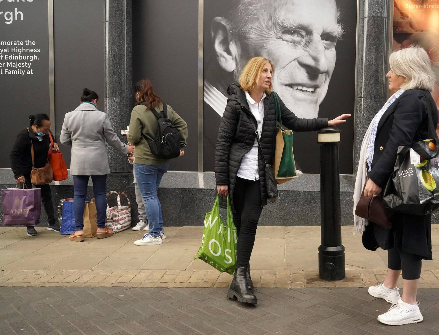 WINDSOR, UNITED KINGDOM - APRIL 16: Shoppers chat next to a photograph commemorating Prince Philip, Duke of Edinburgh, on the window of Marks & Spencer in Windsor High Street on April 16, 2021 in Windsor, United Kingdom. The Queen announced the death of her beloved husband, His Royal Highness Prince Philip, Duke of Edinburgh. HRH passed away peacefully on April 9th at Windsor Castle. (Photo by Christopher Furlong/Getty Images)