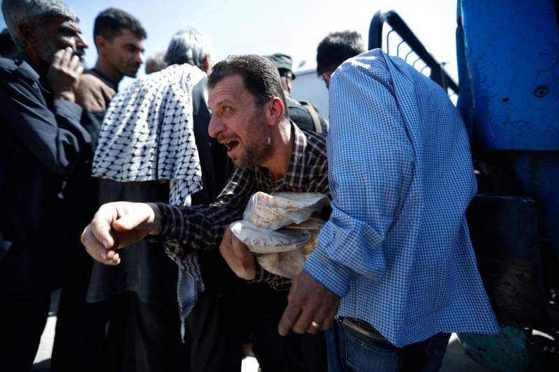 A Syrian man holds bread as Syrian authorities distributed bread, vegetables and pasta to Douma residents, in the town of Douma, the site of a suspected chemical weapons attack, near Damascus, Syria, Monday, April 16, 2018. Two days after Syrian troops declared Douma liberated from opposition fighters, a tour in the city showed the widespread destruction it has suffered since falling under rebel control six years ago. (AP Photo/Hassan Ammar)