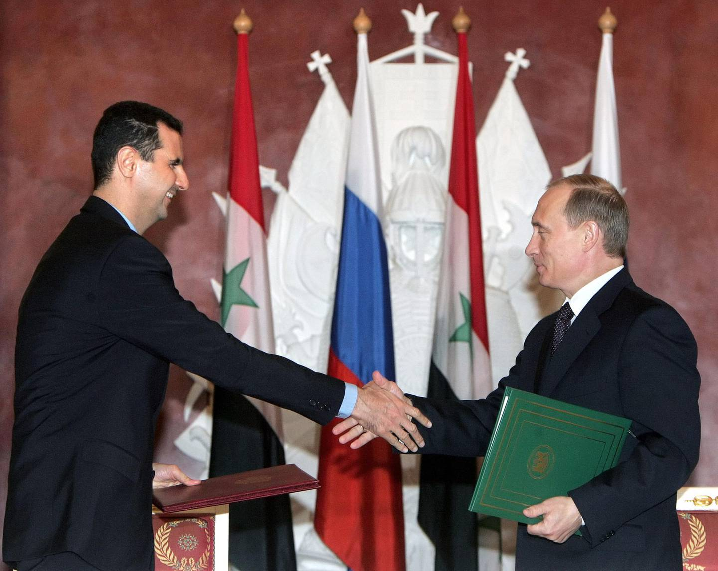 Russian President Vladimir Putin (R) shakes hands with his Syrian counterpart Bashar al-Assad during the signing ceremony in the Moscow's Kremlin, 25 January 2005. Russia and Syria have reached a deal on restructuring debt owed by Syria left over from the Soviet era, the Syrian and Russian presidents announced after Kremlin talks. AFP PHOTO / POOL / SERGEI CHIRIKOV (Photo by SERGEI CHIRIKOV / POOL / AFP)