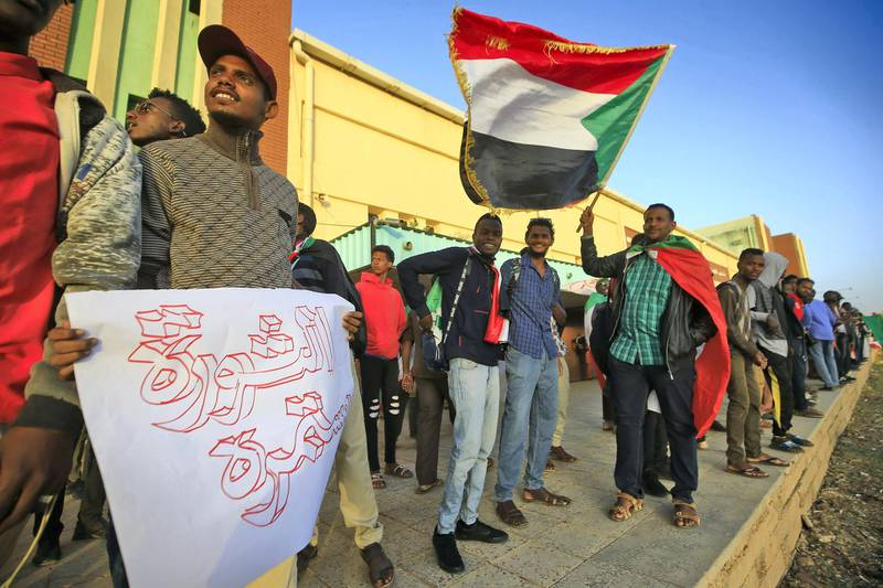 Sudanese protesters wait at a train station in Khartoum to board a train to Atbara on December 19, 2019 to celebrate the one-year anniversary of their protest movement that brought down Omar al-Bashir last April after a thirty-year rule. - A year after demonstrations broke out in Sudan over soaring bread prices, celebrations are planned across the country to mark the uprising that brought down veteran autocrat Bashir. (Photo by ASHRAF SHAZLY / AFP)