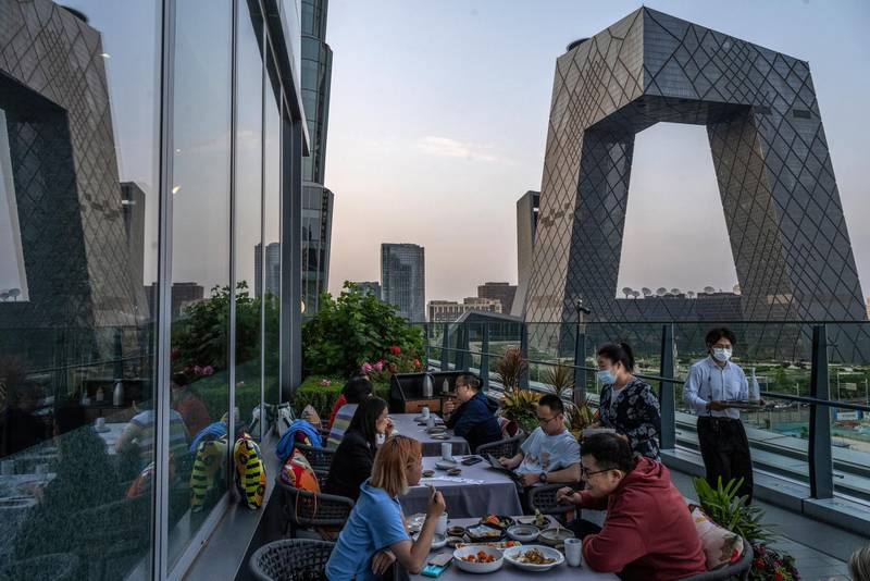 BEIJING, CHINA - MAY 12: People dine at a restaurant overlooking the Central Business District on May 12, 2021 in Beijing, China. China's economy has shown signs of bouncing back as the pandemic is largely under control. (Photo by Kevin Frayer/Getty Images)