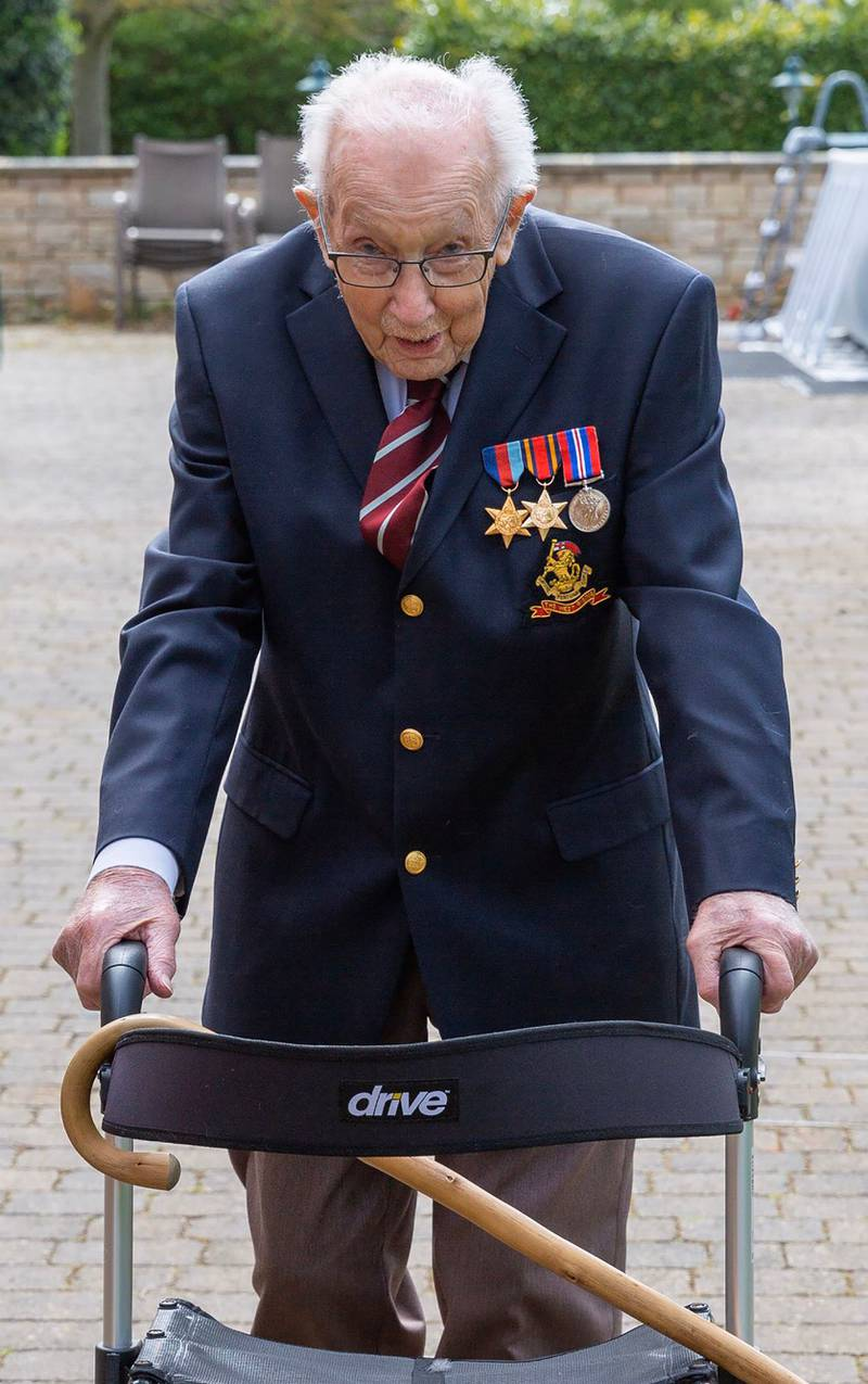 """A handout photo taken in April 2020, and released by the Maytrix Group in London on April 14, 2020, shows World War Two (WWII) veteran 99-year-old Captain Tom Moore walking in his garden in Marston Moretaine, north of London, to raise money for Britain's National Health Service (NHS). A 99-year-old British World War II veteran on Tuesday had raised over £1.5 million ($1.9 million) for health workers on the coronavirus front-line, crashing the donation website hosting his appeal. Tom Moore, a captain who served in India, is being sponsored to complete 100 lengths of his 25-metre garden, with the aid of a frame, in time for his 100th birthday at the end of the month. He originally planned to raise £1,000 for a National Health Service charity after receiving treatment for a broken hip and cancer. But he has now smashed the million mark and completed 70 laps of his garden in Bedfordshire, south England. - RESTRICTED TO EDITORIAL USE - MANDATORY CREDIT """"AFP PHOTO / MAYTRIX GROUP / HANDOUT """" - NO MARKETING - NO ADVERTISING CAMPAIGNS - DISTRIBUTED AS A SERVICE TO CLIENTS  / AFP / MAYTRIX GROUP / - / RESTRICTED TO EDITORIAL USE - MANDATORY CREDIT """"AFP PHOTO / MAYTRIX GROUP / HANDOUT """" - NO MARKETING - NO ADVERTISING CAMPAIGNS - DISTRIBUTED AS A SERVICE TO CLIENTS"""