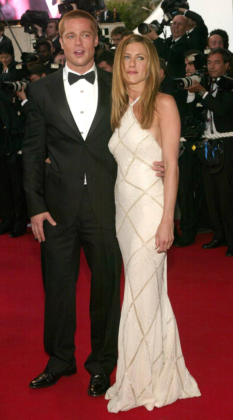 """CANNES, FRANCE - MAY 13:  Actor Brad Pitt and wife actress Jennifer Aniston attend the World Premiere of the epic movie """"Troy"""" at Le Palais de Festival on May 13, 2004 in Cannes, France. Aniston wears a dress by Versace. (Photo by Evan Agostini/Getty Images)"""