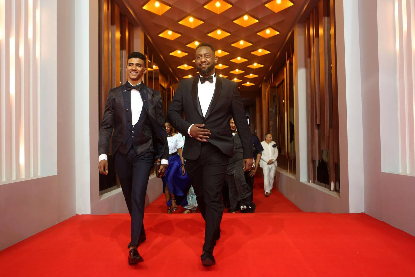 """CORRECTION / Sudanese director Amjad Abu Alaa (R) and actor Hassan Ali walk on the red carpet as they attend the premiere of the movie """"You Will Die at Twenty"""" during the 3rd edition of the Elgouna Film Festival at the Egyptian Red Sea resort of Elgouna on September 20, 2019.  RESTRICTED TO EDITORIAL USE   / AFP / ELGOUNA FILM FESTIVAL / Patrick BAZ / RESTRICTED TO EDITORIAL USE"""
