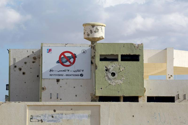 A rocket-riddle building with a sign in Arabic calling for people to stay away from unexploded devices is seen in Tawergha, 260 km east of the Libyan capital Tripoli, on November 9, 2018. Displaced families from Tawergha, a town which sided with Libya's leader Moamer Kadhafi before his ouster in a 2011 revolt, have been able to return to their homes after seven years following an agreement on a deal that allowed civilians to return to their hometown.. / AFP / Mahmud TURKIA
