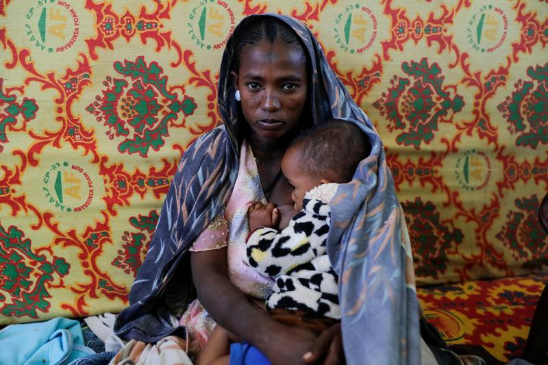 """A woman holds an infant inside the Adiha secondary school, which was turned into a temporary shelter for people displaced by conflict, in the city of Mekelle, Tigray region, Ethiopia, March 12, 2021. REUTERS/Baz Ratner     SEARCH """"RATNER TIGRAY"""" FOR THIS STORY. SEARCH """"WIDER IMAGE"""" FOR ALL STORIES"""