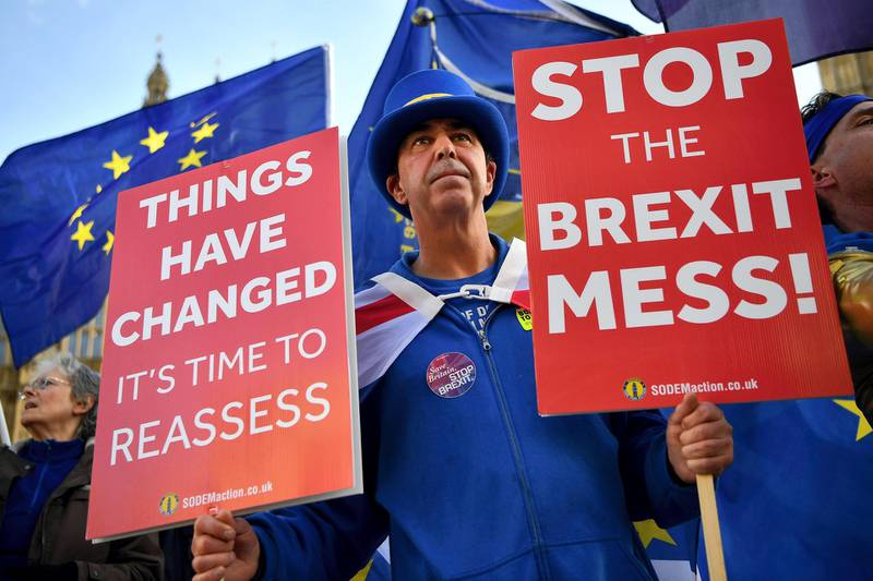 Pro-European Union (EU), anti-Brexit demonstrator Steve Bray holds placards and wave Union and EU flags as they protest outside of the Houses of Parliament in London on November 14, 2018. - British and European Union negotiators have reached a draft agreement on Brexit, Prime Minister Theresa May's office said on November 13. (Photo by Ben STANSALL / AFP)