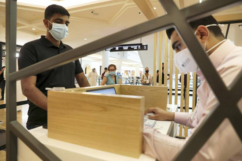 DUBAI, UNITED ARAB EMIRATES , October 14 – 2020 :- Anto Antony (left) taking the token for his COVID-19 nasal swab test at the COVID 19 testing station set up at Mall of the Emirates in Dubai. (Pawan Singh / The National) For News/Online. Story by Sarwat