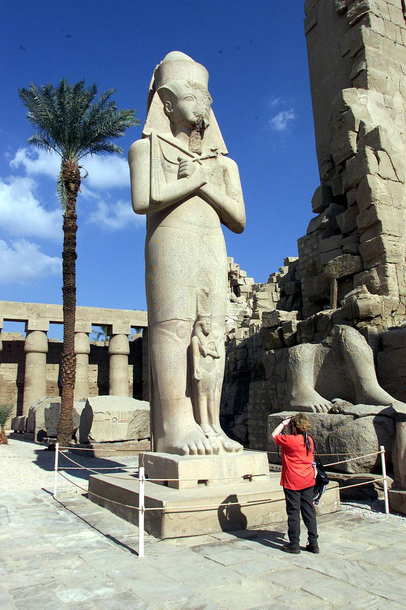 A visitor takes a picture of Pharaoh King Ramses II's statue at Karnak temple January 13, 2002. The temple, about 4000 years old, was renovated and reopened to the public. REUTERS/Aladin Abdel Naby  AN/CLH/