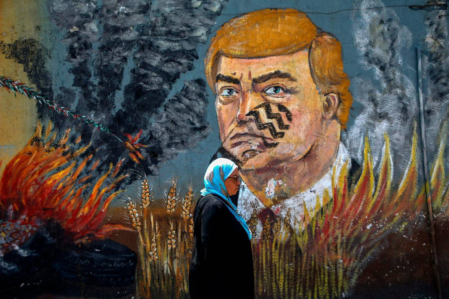 A Palestinian woman walks past a graffiti depicting US President Donald Trump with a footprint on his face in Gaza City on June 23, 2019. The United States is set to co-chair a two-day conference in Bahrain from June 25 focusing on the economic aspects of President Donald Trump's Israeli-Palestinian peace plan. The Palestinians confirmed in May they will not participate in the conference, adding they were not consulted beforehand. / AFP / MOHAMMED ABED