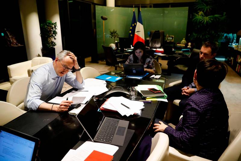 French Economy and Finance Minister Bruno Le Maire (L) speaks on the phone with his German counterpart as his advisor Juliette Oury (C), his cabinet director Emmanuel Moulin (2nd R) and French Treasury director Odile Renaud-Basso attend, during a break in a videoconference meeting of the Eurogroup of eurozone finance ministers to discuss coronavirus response on April 7, 2020 at the French Economy ministry in Paris. EU finance ministers hope to agree a coronavirus economic rescue package for the worst-hit member states on Tuesday, but will fall short of demands from beleaguered Spain and Italy. / AFP / Thomas SAMSON
