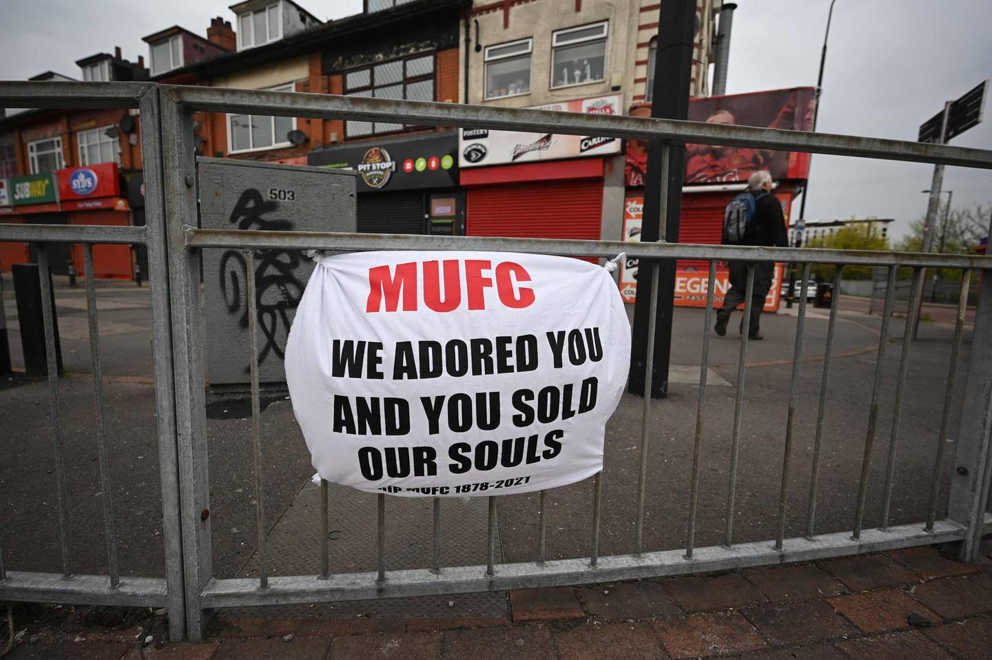 A banner against the proposed European Super League hangs from railings close to Manchester United's Old Trafford stadium in Manchester, northwest England on April 21, 2021.  The proposed European Super League (ESL) appeared dead in the water today after all six English clubs withdrew following a furious backlash from fans and threats from football authorities. / AFP / Oli SCARFF