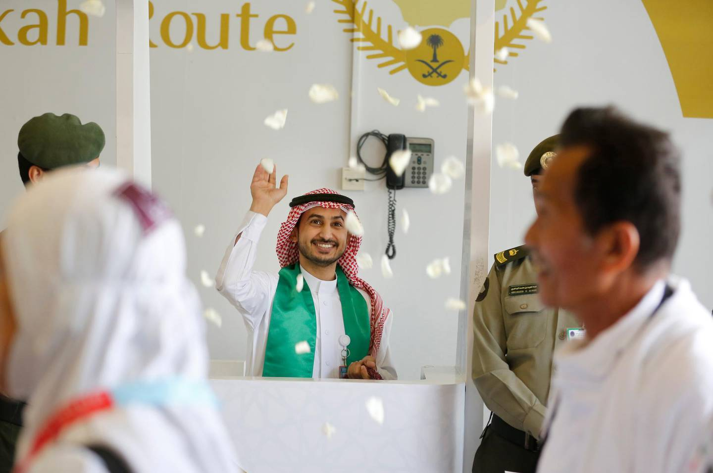 A Saudi airport worker throws flowers as he welcomes Malaysian pilgrims at the Hajj Terminal at Jiddah airport, Saudi Arabia, Saturday, Aug. 3, 2019.  The annual Islamic pilgrimage draws millions of visitors each year, making it the largest yearly gathering of people in the world.  (AP Photo/Amr Nabil)