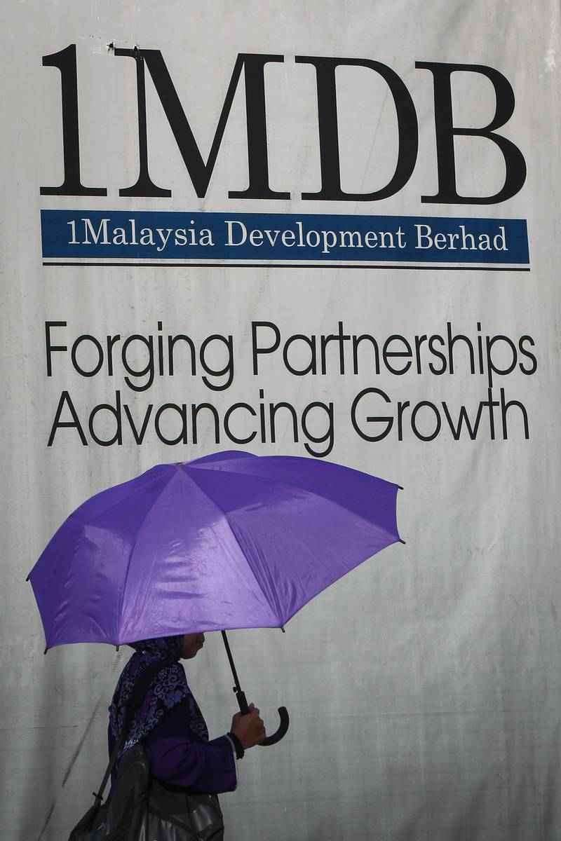 In this July 8, 2015, photo, a Malaysian Muslim woman walks past a 1Malaysia Development Berhad (1MDB) billboard at the flagship's development site in Kuala Lumpur, Malaysia. Malaysia's image as a striving, modern nation that upholds the rule of law has been undermined by an epic corruption scandal at state investment fund 1MDB. Prime Minister Najib Razak, who set up the fund, is facing May 9, 2018 national elections that will test his legitimacy. (AP Photo/Joshua Paul)