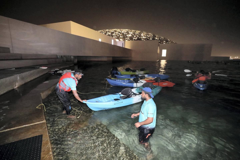Abu Dhabi, United Arab Emirates - August 15, 2019: People kayaking around Louvre Abu Dhabi at night. Thursday the 15th of August 2019. Louvre, Abu Dhabi. Chris Whiteoak / The National