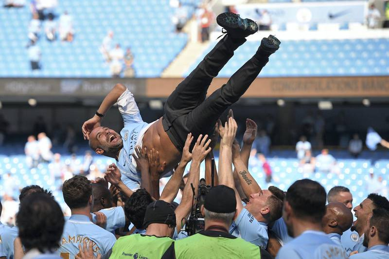 Manchester City's Spanish manager Pep Guardiola is tossed by Manchester City players during the trophy ceremony after the English Premier League football match between Manchester City and Huddersfield Town at the Etihad Stadium in Manchester, north west England, on May 6, 2018. (Photo by Oli SCARFF / AFP) / RESTRICTED TO EDITORIAL USE. No use with unauthorized audio, video, data, fixture lists, club/league logos or 'live' services. Online in-match use limited to 75 images, no video emulation. No use in betting, games or single club/league/player publications. /