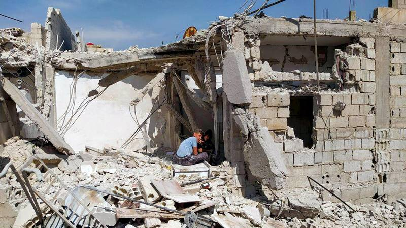 """A handout picture released by the official Syrian Arab News Agency (SANA) on April 27, 2020 shows a two youth sitting amid the debris of a building after an Israeli air strike, south of the Syrian capital Damascus. - Israeli air strikes near the Syrian capital early Monday killed three civilians, state media said. """"Three civilians were martyred and four others wounded, including a child, because shrapnel from Israeli missiles fell on houses"""" in the suburbs of Damascus, the official SANA news agency said. Syrian air defences had downed """"most"""" of the Israeli missiles launched from Lebanese air space shortly before dawn, SANA said in an earlier report. (Photo by - / various sources / AFP) / == RESTRICTED TO EDITORIAL USE - MANDATORY CREDIT """"AFP PHOTO / HO / SANA"""" - NO MARKETING NO ADVERTISING CAMPAIGNS - DISTRIBUTED AS A SERVICE TO CLIENTS =="""