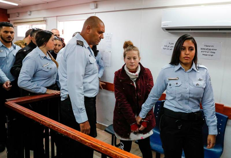 Palestinian Ahed Tamimi (2nd-R), 17, a well-known campaigner against Israel's occupation, appears at a military court at the Israeli-run Ofer prison in the West Bank village of Betunia on December 20, 2017.  Israel's army arrested Tamimi on December 19, 2017, after a video went viral of her slapping Israeli soldiers in the occupied West Bank as they remained impassive. / AFP PHOTO / AHMAD GHARABLI