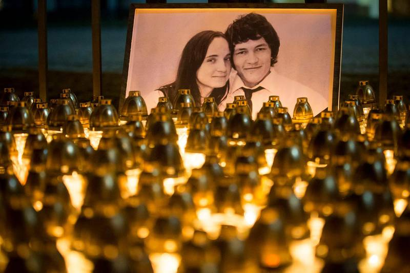 Light tributes placed during a silent protest in memory of murdered journalist Jan Kuciak and his girlfriend Martina Kusnirova, seen in photo, in Bratislava, Slovakia, on Wednesday, Feb. 28, 2018.  Investigative journalist Kuciak was shot dead in Slovakia last week while working on a story about the activities of Italian mafia in Slovakia and their alleged links to people close to Prime Minister Robert Fico.(AP Photo/Bundas Engler)