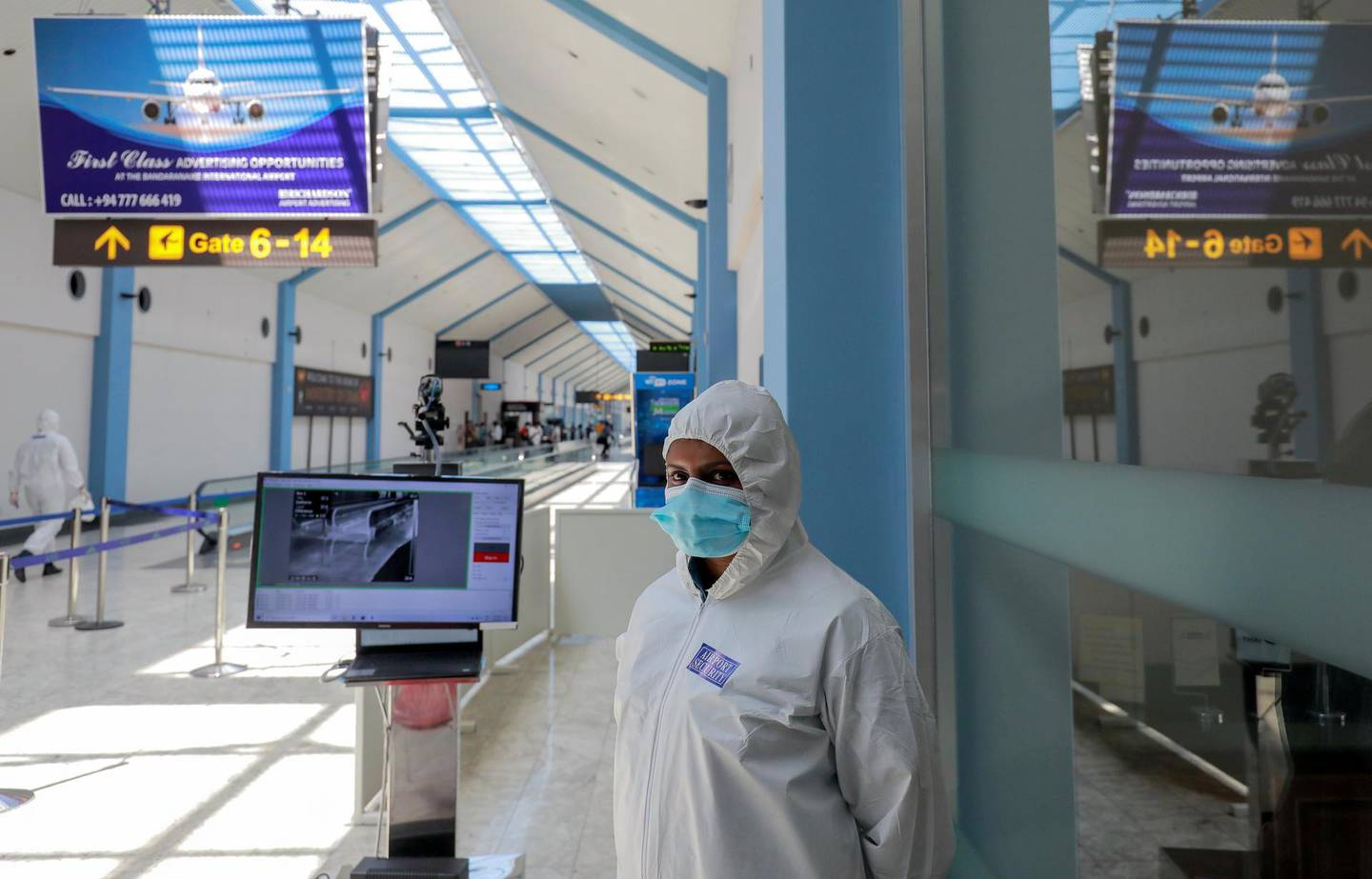 A security officer wearing protective gear stands next to passenger temperature scanning machine where she is on duty as Sri Lanka's government scheduled to reopen the country's airports for tourists from January 21, 2021, as they were closed since March 2020 due to spread of  coronavirus disease (COVID-19), at Bandaranaike International Airport in Katunayake, Sri Lanka January 20, 2021. REUTERS/Dinuka Liyanawatte