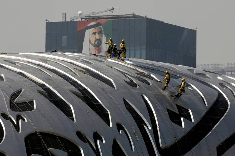 Workers clean the fascade of The Museum of the Future within sight of a portrait of Prime Minister and Vice-President of the United Arab Emirates and ruler of Dubai Sheikh Mohammed bin Rashid al-Maktoum in Dubai, United Arab Emirates, June 9, 2021. Picture taken June 9, 2021. REUTERS/Christopher Pike