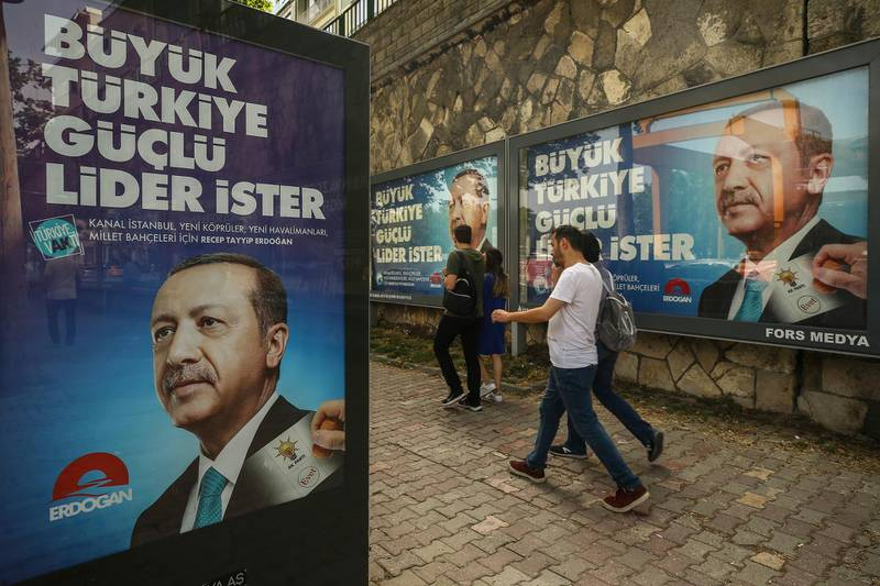 In this photo taken on Saturday, June 9, 2018, people walk past election posters of Turkey's President Recep Tayyip Erdogan and his ruling Justice and Development (AKP) Party in Istanbul. The most powerful and polarizing leader in Turkish history is standing for re-election in a presidential vote on Sunday that could cement Turkey's switch from a parliamentary to a presidential system, which was narrowly approved in a referendum last year. (AP Photo/Emrah Gurel)