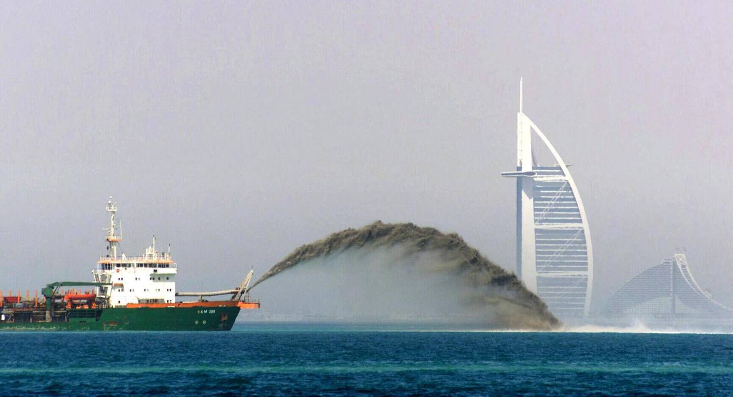 A dredger barge pumps sand onto the sea bed 3 miles off the shore of Dubai as the Palm Island development gets in full gear 05 May 2002, with the Burj al-Arab and Jumairah beach hotels in the background. The ambitious project comprises the creation of an palm tree-shaped artificial island on which there will be hotels, beaches, marinas and residential buildings.     AFP PHOTO/Jorge FERRARI (Photo by JORGE FERRARI / AFP)