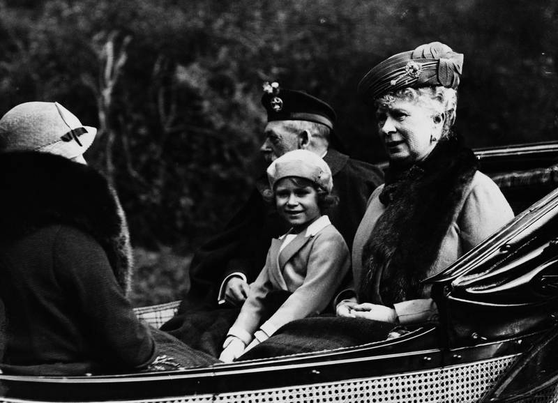 Princess Elizabeth (later Queen Elizabeth II) seated between her grandfather King George V (1865-1936) and grandmother Queen Mary of Teck (1867-1953) as they ride in a carriage back to Balmoral Castle from Crathie Kirk near Braemar in Scotland in August 1935. (Photo by Topical Press Agency/Getty Images)