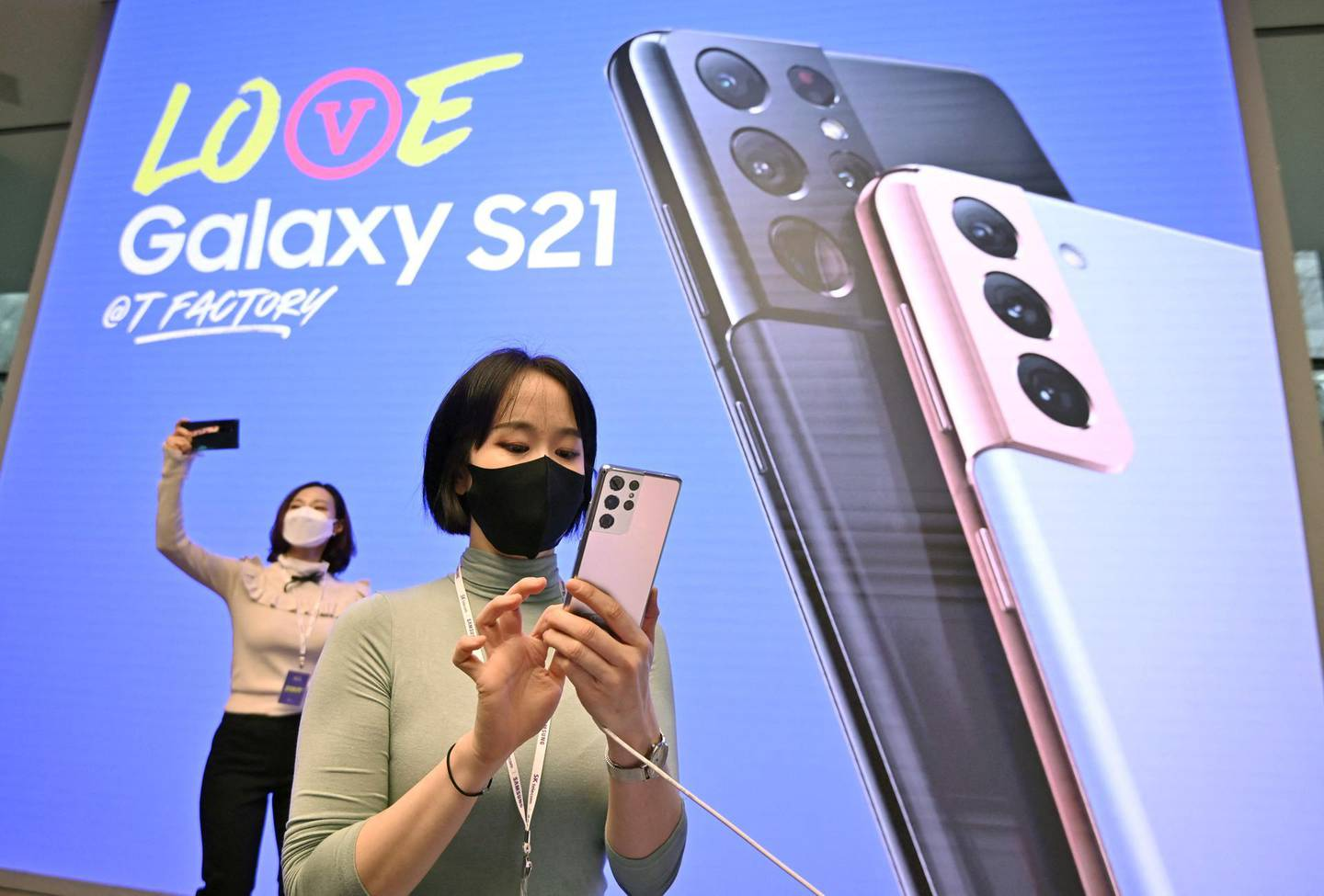 A woman looks at the Samsung Galaxy S21 smartphone during a domestic launch event at a flagship store of SK Telecom in Seoul on January 22, 2021. (Photo by Jung Yeon-je / AFP)