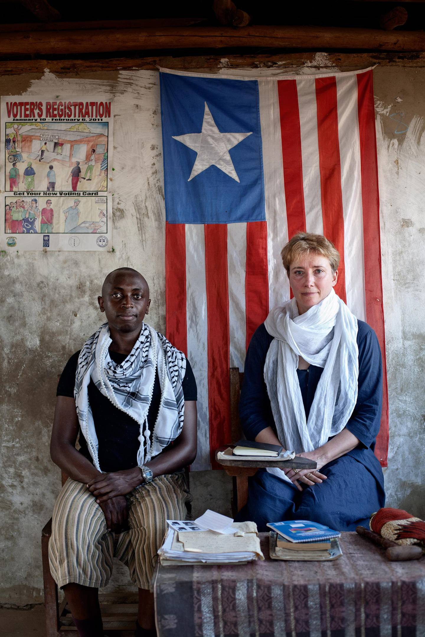 Emma Thompson and her adopted son Tindyebwa Agaba, who is known as Tindy, sit infront of the Liberian flag that hangs in Maime Smith's front porch in Zannah village, Monserrado county, Liberia.