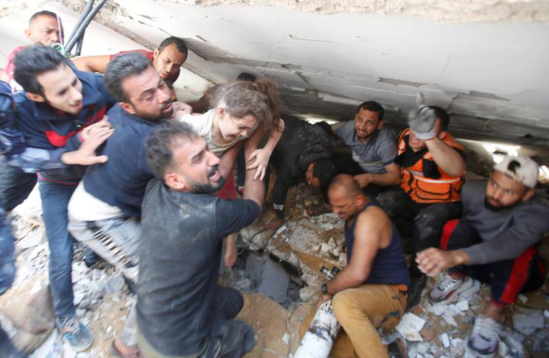 Rescuers carry a girl as they search for victims amid rubble at the site of Israeli air strikes, in Gaza City May 16, 2021. REUTERS/Mohammed Salem