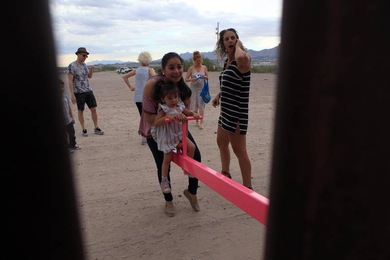 """American and Mexican families play with a toy called """"up and down"""" (Seesaw swing) over the Mexican border with US at the Anapra zone in Ciudad Juarez, Chihuahua State, Mexico on July 28, 2019. (Photo by LUIS TORRES / AFP)"""