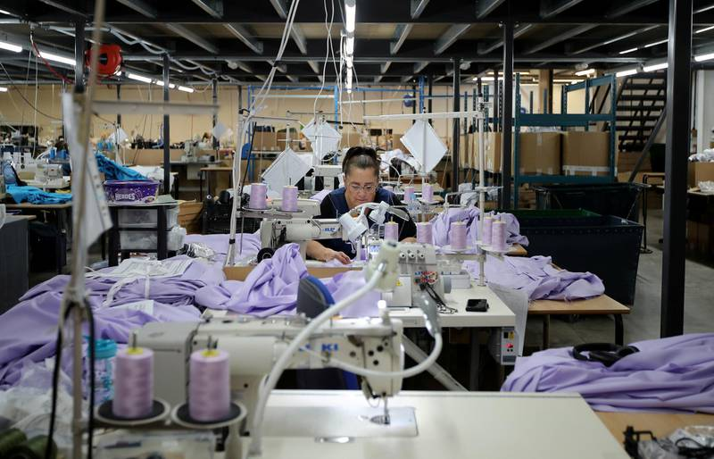 FILE PHOTO: Tibard employees make NHS uniforms at their factory in Dukinfield as the spread of the coronavirus disease (COVID-19) continues, Dukinfield, Britain, April 6, 2020. REUTERS/Molly Darlington/File Photo  GLOBAL BUSINESS WEEK AHEAD