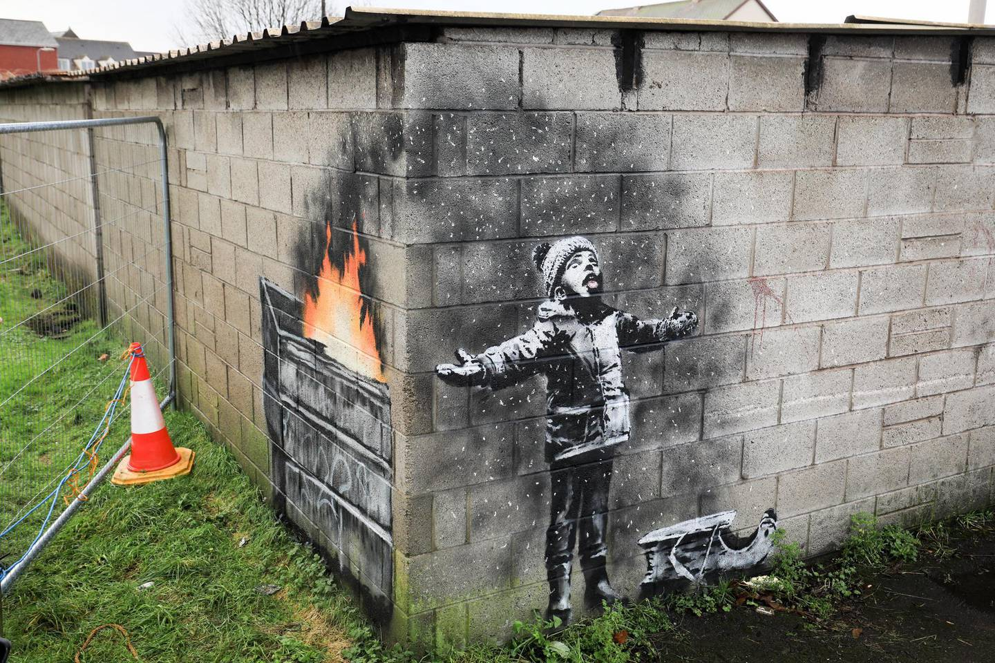 """PORT TALBOT, WALES - DECEMBER 20: People gather around fences that have been erected to protect the latest  piece of artwork by the underground guerrilla artist Banksy on December 20, 2018 in Port Talbot, Wales. The British graffiti artist who keeps his identity a secret, confirmed yesterday that the artwork was his using his verified Instagram account to announce """"Season's greetings"""" with a video of the artwork in Port Talbot. (Photo by Matt Cardy/Getty Images)"""