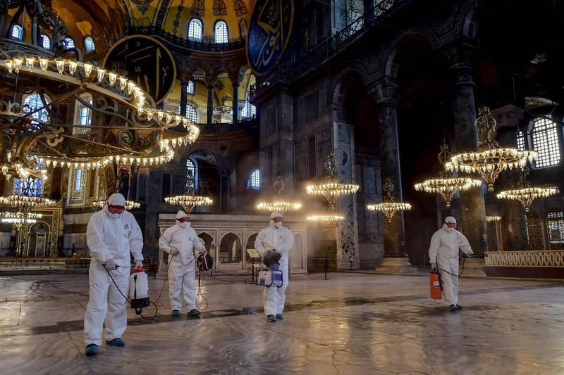 TOPSHOT - Employees of the Fatih Municipality wearing protective suits disinfect the Hagia Sophia to prevent the spread of the COVID-19, caused by the novel coronavirus, in Istanbul, on March 13, 2020. Turkey announced on March 11, 2020 its first coronavirus case, a man who had recently travelled to Europe and is in good health. Turkey has announced several measures in recent weeks to try and stop the virus reaching the country, including thermal cameras at airports, cancelling flights to affected countries and closing its border with Iran. / AFP / Yasin AKGUL