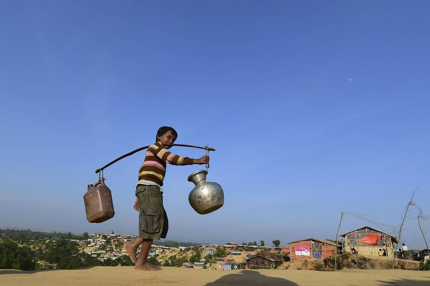 """TOPSHOT - A Rohingya refugee child walks back to his makeshift shelter after collecting water at Hakimpara refugee camp in Bangladesh's Ukhia district on January 27, 2018. The repatriation of hundreds of thousands of Rohingya Muslims who fled violence in Myanmar will not begin as planned, Bangladesh said January 22, with authorities admitting """"a lot of preparation"""" was still needed. / AFP PHOTO / Munir UZ ZAMAN"""