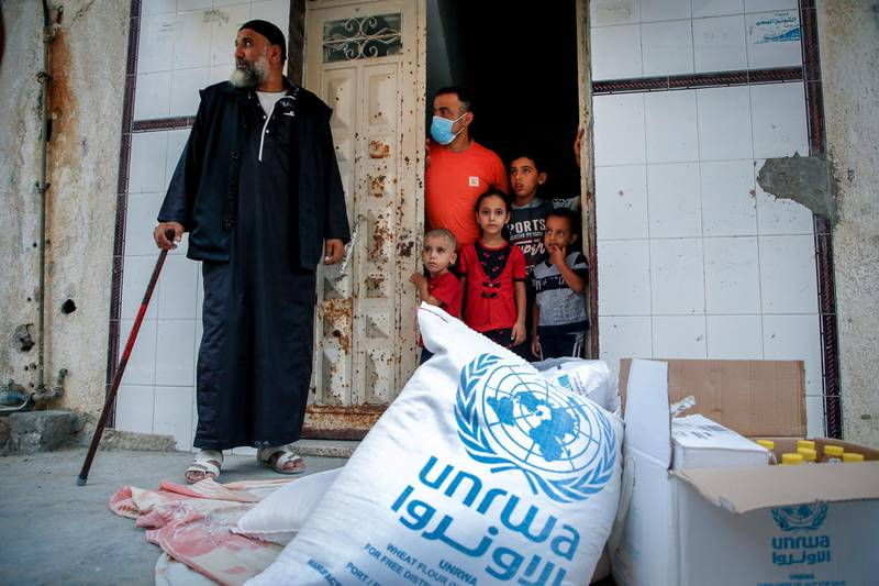 Members of a Palestinian family, some clad in mask due to the COVID-19 coronavirus pandemic, stand through the door of their home as they receive food aid provided by the United Nations Relief and Works Agency for Palestine Refugees (UNRWA) in Gaza City on September 15, 2020. (Photo by MOHAMMED ABED / AFP)
