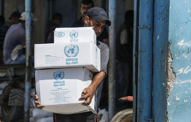 A Palestinian man transports boxes of food outside an aid distribution centre run by the United Nations Relief and Works Agency (UNRWA) in the central Gaza Strip refugee camp of Bureij, on July 31, 2019.  An internal ethics report has alleged mismanagement and abuses of authority at the highest levels of the UN agency for Palestinian refugees even as the organisation faced an unprecedented crisis after US funding cuts. Lacking natural resources, the Gaza Strip suffers from a chronic shortage of water, electricity and petrol. More than two-thirds of the population depends on humanitarian aid.  / AFP / SAID KHATIB