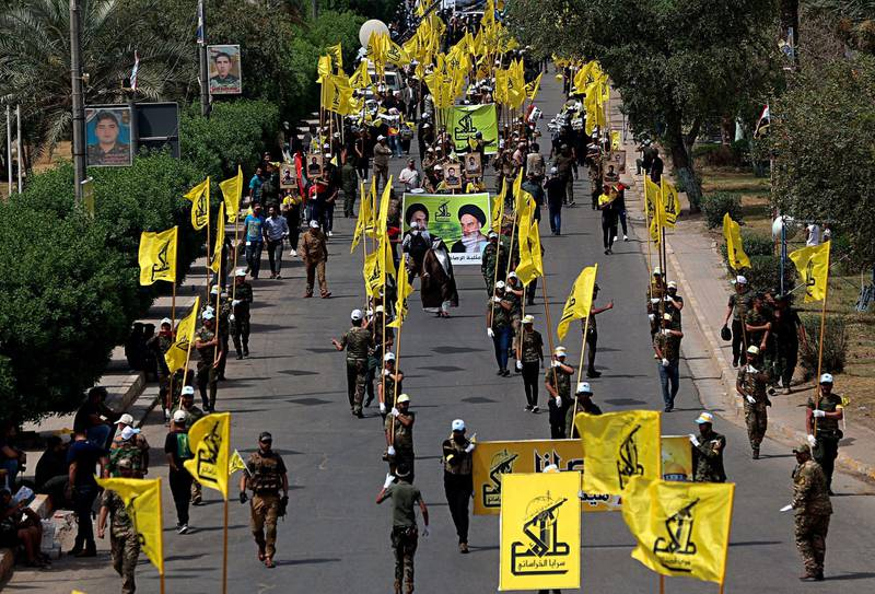 """Iraqi Popular Mobilization Forces march as they hold Popular Mobilization flags and posters of Shiites spiritual leaders during """"al-Quds"""" Day, Arabic for Jerusalem, in Baghdad, Iraq, Friday, June 8, 2018. Jerusalem Day began after the 1979 Islamic Revolution in Iran, when the Ayatollah Khomeini declared the last Friday of the Muslim holy month of Ramadan a day to demonstrate the importance of Jerusalem to Muslims. (AP Photo/Hadi Mizban)"""