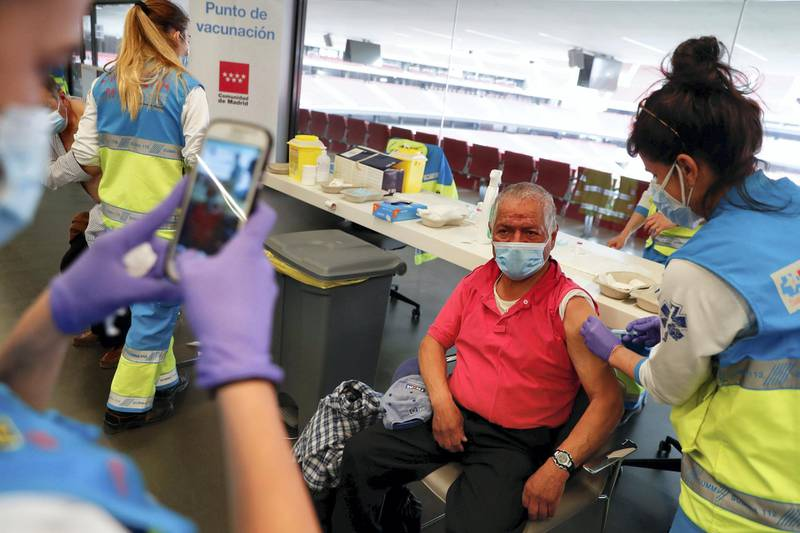 An elderly man receives an injection with AstraZeneca's COVID-19 vaccine at a vaccination centre, at the Wanda Metropolitano stadium, in Madrid, Spain, March 31, 2021. REUTERS/Susana Vera