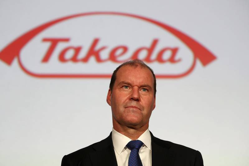 Takeda Pharmaceutical company's president and chief executive officer Christophe Weber stands before a company logo after a press conference in Tokyo on May 9, 2018. Drug giant Takeda on May 8 said it would buy Irish pharmaceuticals firm Shire in a deal worth 62.5 billion USD, the biggest foreign takeover ever by a Japanese firm. / AFP PHOTO / Behrouz MEHRI