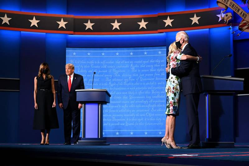 """(FILES) In this file photo taken on October 22, 2020, US First Lady Melania Trump (L) stands with US President Donald Trump as Jill Biden (R) hugs husband Democratic Presidential candidate Joe Biden at the end of the final presidential debate at Belmont University in Nashville, Tennessee. Jill Biden is no stranger to the glare of the political spotlight. Her husband has been a Washington insider since they wed in 1977, and she was America's second lady for eight years. But if Joe Biden wins the White House, his 69-year-old wife will have the opportunity to push the role of first lady into the 21st century -- by keeping her full-time job as a professor. """"Most American women have both a work life and a family life, but first ladies have never been allowed to do so,"""" said Katherine Jellison, a history professor at Ohio University. / AFP / Jim WATSON"""